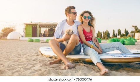 young hipster couple on beach playing with dog Shih Tzu breed, smiling, happy, having fun, summer casual style, romantic mood, family together, sunglasses, surf board, hugging, denim jeans