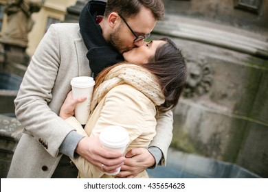 Young hipster couple with take away coffee kissing and hugging in old town