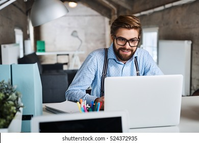 Young hipster, designer working on laptop at creative agency office