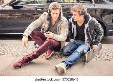 Young hipster fashion brothers having fun using smartphone - Best friends sharing time with smart phone - Everyday life moment with modern device - Light vintage filtered look with soft focus on faces