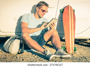 Young hipster fashion guy with computer tablet sitting next his car during road trip - Concept of new trends and technology mixed with vintage lifestyle - Traveler man on retro nostalgic filtered look