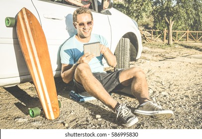 Young hipster fashion guy working remote on computer tablet sitting at car on road trip - New trend and technology concept with digital nomad lifestyle - Traveler man on retro contrasted filtered look
