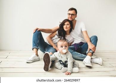 Junge Hipster-Vater, Mutter und süßer kleiner Junge auf rustikalem Holzboden auf weißem Hintergrund