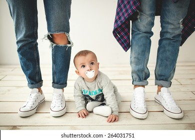Young hipster father, mother and cute baby boy on rustic wooden floor over white background