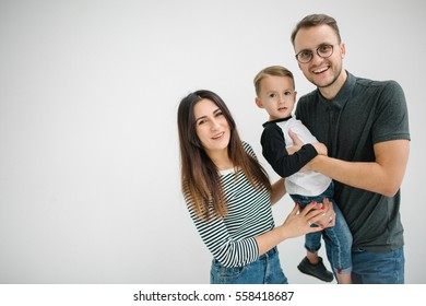 Young hipster father, mother holding cute baby boy on concrete floor over white background