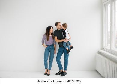Junge Hip-Vater, Mutter, die einen süßen Baby hält, auf betoniertem Boden auf weißem Hintergrund