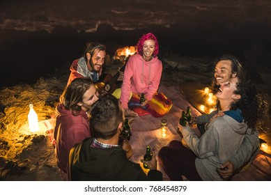 Young hipster friends having fun together at beach camping party with night campfire light - Friendship travel concept with young people traveler drinking beer at summer surf bonfire - High iso image