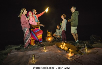 Young hipster friends having fun together at beach camping party with night campfire light - Friendship travel concept with young surfer people grilling corn cob at summer barbecue - High iso image