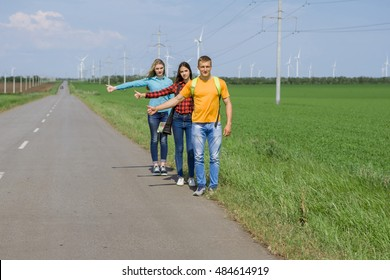 Young hipster friends on road. Two girls and a guy travel hitchhikers