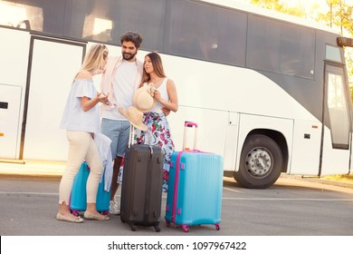 Young hipster friends travel on vacation by bus, they standing front of bus and waiting for go-off