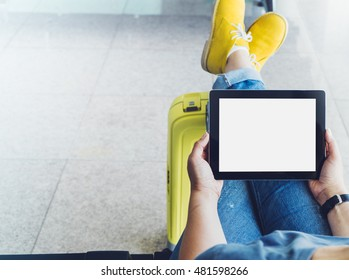 Young hipster girl at airport in yellow boot on suitcase waiting air flight, female hands holding computer in terminal departure lounge gate, traveler trip concept, mock up of blank screen tablet