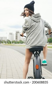 Young hipster girl with black bike back to camera. Outdoor lifestyle portrait