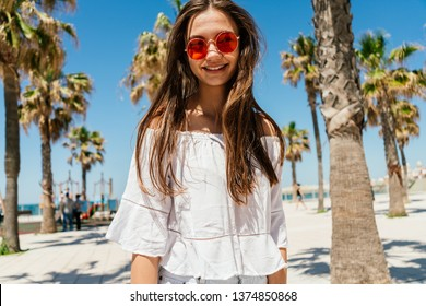 Young hipster girl in bright glasses on the background of palm trees dressed in a white shirt, laughing. Summer carefree vacation time