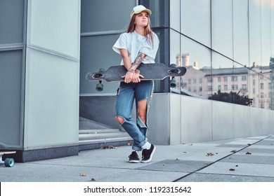 Young hipster girl in cap dressed in a white shirt and ripped jeans holds skateboard while posing near skyscraper.