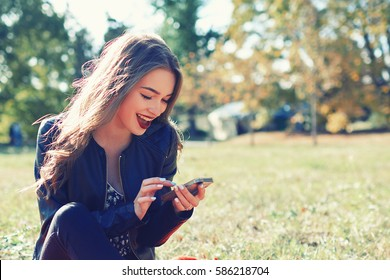 Young hipster girl is chatting via mobile phone in network with her friends and listening to music , pretty female is reading text message on her cell telephone while relaxing in the park