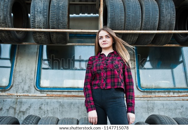 Young hipster girl in checkered shirt at tire fitting zone.