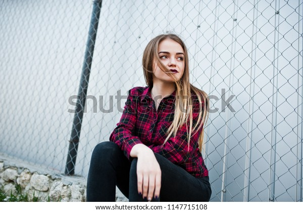 Young hipster girl in checkered shirt posed outdoor.