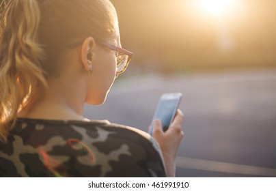 Young hipster girl checks mail using smartphone outdoors. Soft focus