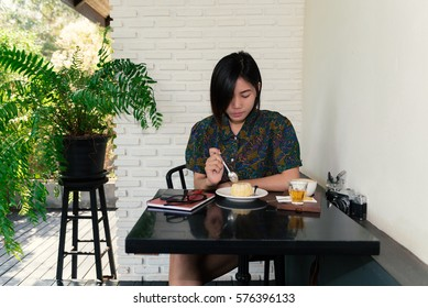 Young hipster girl eats tasty cake and drinking a hot drink in a nice cafe