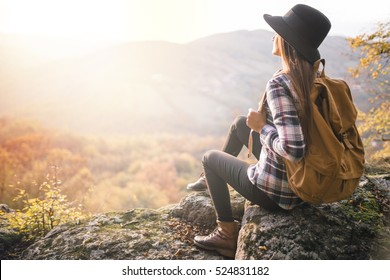 Young hipster girl enjoy sunset on viewpoint. Travel woman with backpack and hat