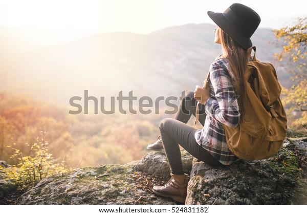 Junge Hipster Mädchen genießen Sonnenuntergang auf Sicht. Reisende mit Rucksack und Hut