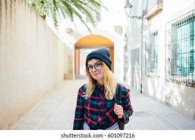 Young hipster girl in flannel, beanie and glasses standing in a bright sunlit alley with colors and palm tree