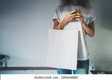Young hipster girl is holding a blank white  paper bag in her hands with an empty space for logo and design.Cropped photo of a girl using modern smartphone. home interior, white background