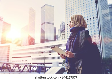 Young hipster girl is holding digital tablet and looking in window at active life of big metropolitan city with tall skyscrapers,background with copy space for your advertising text message or content