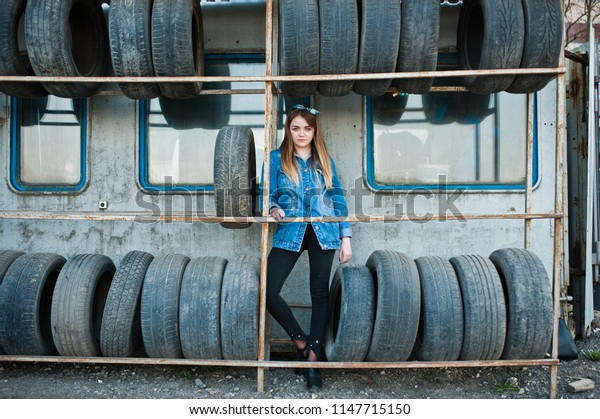Young hipster girl in jeans jacket and head scarf at tire fitting zone.