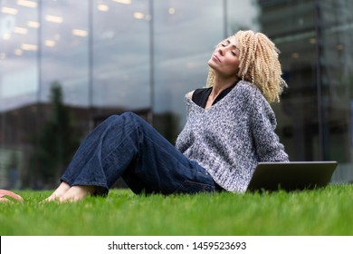 young hipster girl with laptop sits on grass near business center. Afro hair curls. Work in open space. student, learning