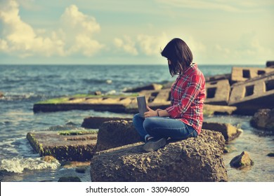 young hipster girl with laptop sitting on rock. Vintage photo