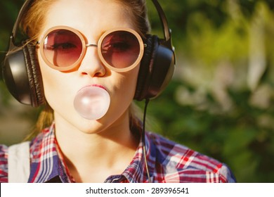 Young hipster girl listening to music on headphones in a summer park. Portrait close-up with chewing gum. Warm toning. Concept of cheerful youth.