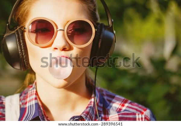 Jeune fille branchée écoutant de la musique sur un casque dans un parc d'été. Portrait en gros plan avec chewing-gum. Chaleureux. Concept de jeunesse joyeuse.