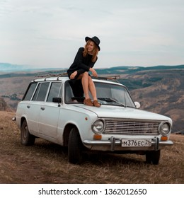 Young hipster girl in love sitting on the roof of vintage car on mountain background. Traveling, activism and friendship concept.