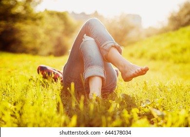 Young hipster girl lying on the grass at sunset summer time