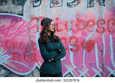 Young hipster girl on background of graffiti.