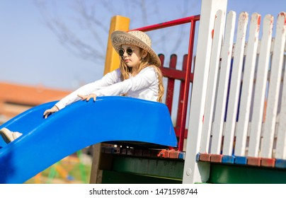 Young hipster girl at playground. Girl with sunglasses and hat playing outdoor
