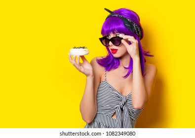 Young hipster girl with purple hair holding a cream cake on yellow background