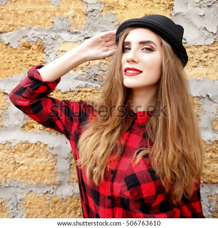 7048599e31c Young hipster girl in red plaid shirt with hat having fun. Beautiful  fashionable woman stands