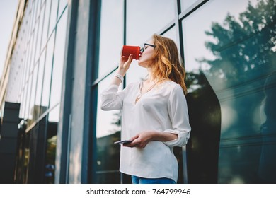 Young hipster girl resting outdoors enjoying favorite beverage while waiting for telephone call, woman standing on urban settings background drinking coffee to go spending free time on street
