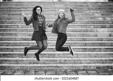 A young hipster girl is riding a skateboard. Girls girlfriends for a walk in city with a skateboard. Spring sports on the street with a skateboard.