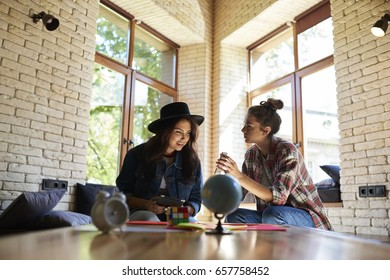 Young hipster girl showing useful application to her best friend on mobile phone while sitting in cozy loft interior. Attractive cute brunette woman atently looking at smartphone connected to internet