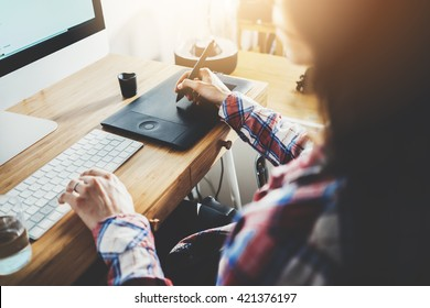 Young hipster girl sitting at her workspace and using modern computer and digital graphic tablet while working at vintage loft, professional female graphic designer working at home, flare light