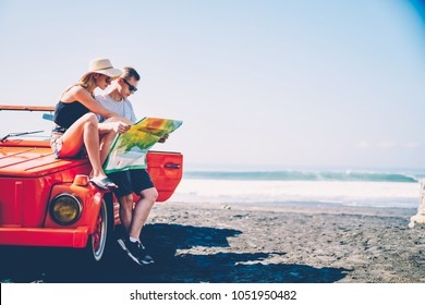Young hipster girl sitting on vintage convertible car reading map with her boyfriend, romantic couple searching route for explore tropical island on rental automobile making stop on ocean beach