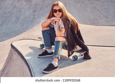 Young hipster girl in sunglasses dressed in ripped jeans and white shirt sitting on a longboard at skatepark.