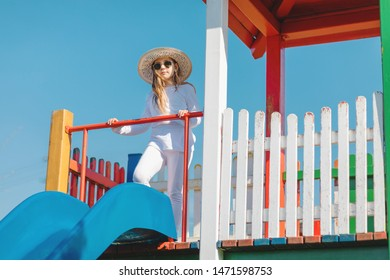 Young hipster girl with sunglasses and hat on playground