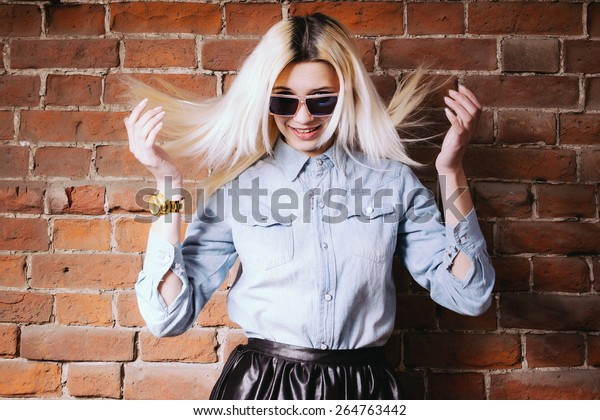 Young hipster girl in sunglasses  shaking her head, hair fly in the air, dishevelled street fashion look, copy space on red brick wall