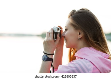 Young hipster girl takes pictures outdoors. Female photographer with film camera in her hands. Soft focus