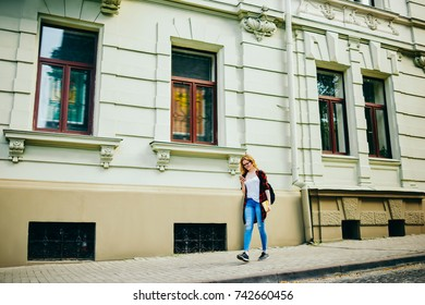 Young hipster girl walking on street passing architecture buildings on street using mobile application for searching direction,traveler in casual outfit strolling during free time on urban settings