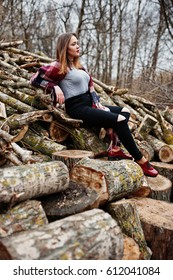 Young hipster girl wear on blanket against wooden stumps on wood.